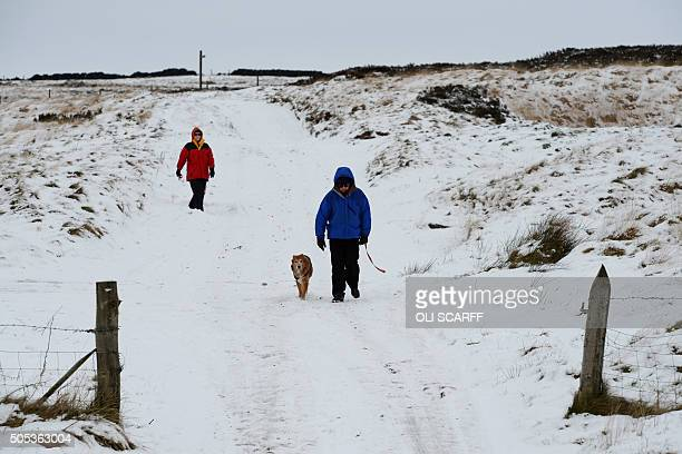 Walkers negotiate the snow covering the ground on Wessenden Moor near the village of Marsden near Huddersfield northern England on January 17 2016...