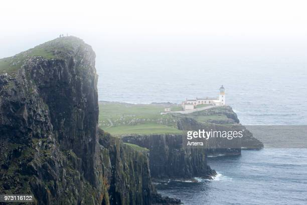 Walkers on clifftop watching Neist Point Lighthouse in the mist on the Isle of Skye Inner Hebrides Scottish Highlands Scotland UK