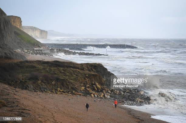 Walkers on the beach below the fenced off area around the cliff fall on November 15, 2020 in Eype, Dorset. A large section of a cliff on Dorset's...