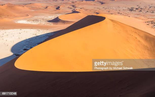 Walkers on the ridge of a giant sanddune in the Namib Desert, Namibia