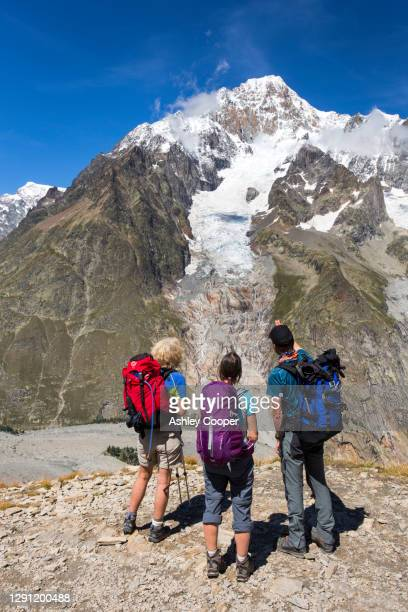 walkers on the tour de mont blanc ascending out of the vallon de la lex blanche in italy, below mont blanc with a guide pointing out the rapidly retreating glacier. - retreating ストックフォトと画像