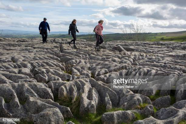 Walkers pass over the limestone pavement at Ing Scar near Malham in the Yorkshire Dales National Park, on 12th April 2017, in Malham, Yorkshire,...