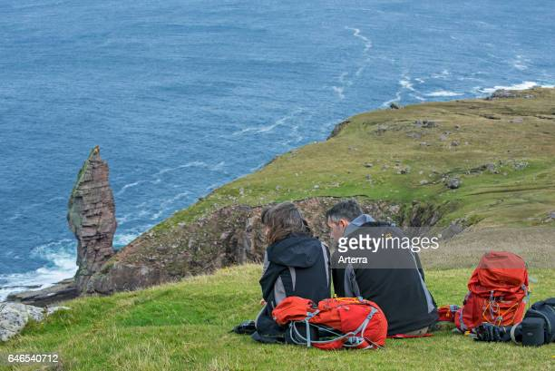 Walkers resting near the Old Man of Stoer 60 metres high sea stack of Torridonian sandstone at the Point of Stoer in Sutherland Scottish Highlands...