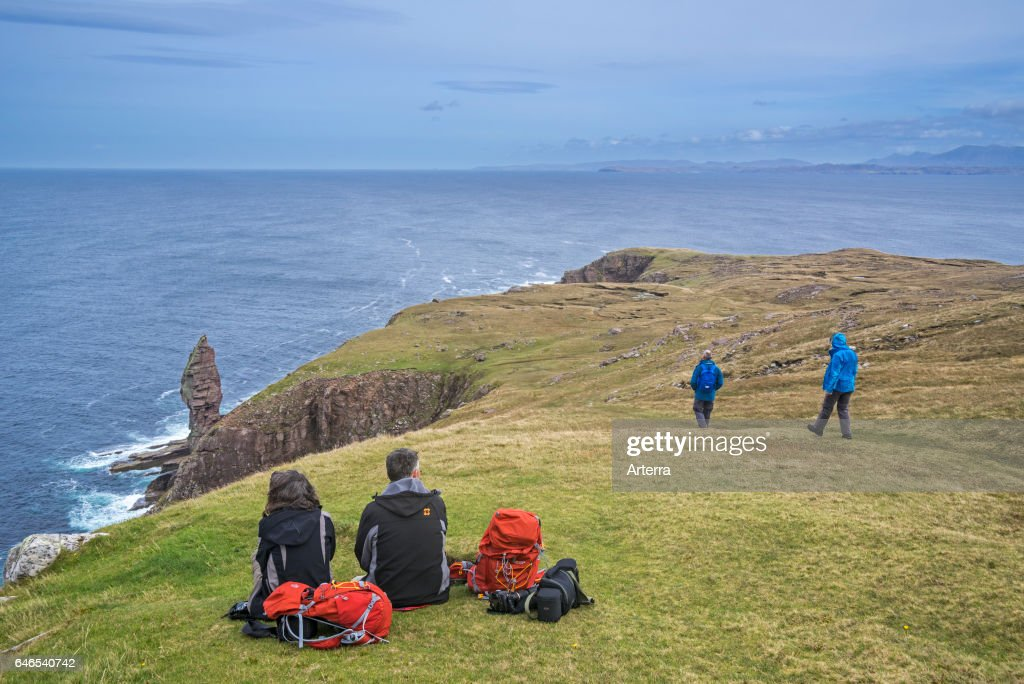 Walkers resting near the Old Man of Stoer. : News Photo
