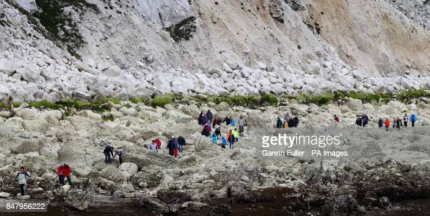 Walkers scramble over rocks as they head for the Lighthouse at Beachy Head in Eastbourne Sussex as over 200 people took advantage of a low spring...
