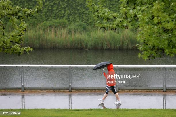 Walkers shelter from the rain under umbrellas on April 28, 2020 in London, England. British Prime Minister Boris Johnson, who returned to Downing...
