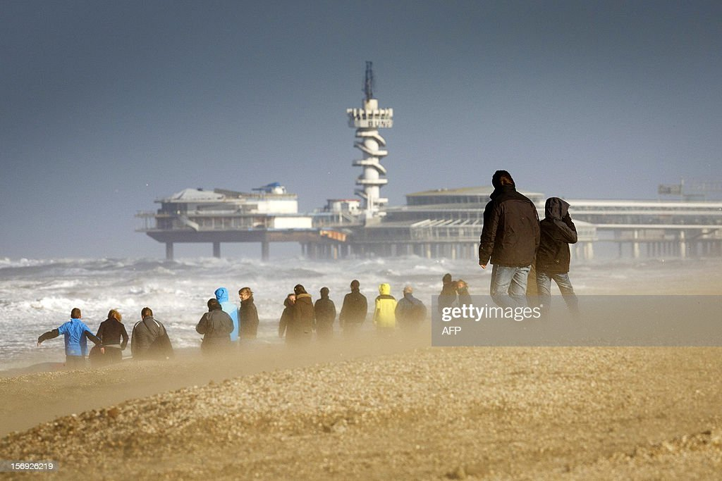 Walkers stroll on the beach at the coastal town of Scheveningen, near The Hague, The Netherlands, on November 25, 2012. A storm rages about the Netherlands, especially in the coastal provinces with gusts of wind and wind force nine.