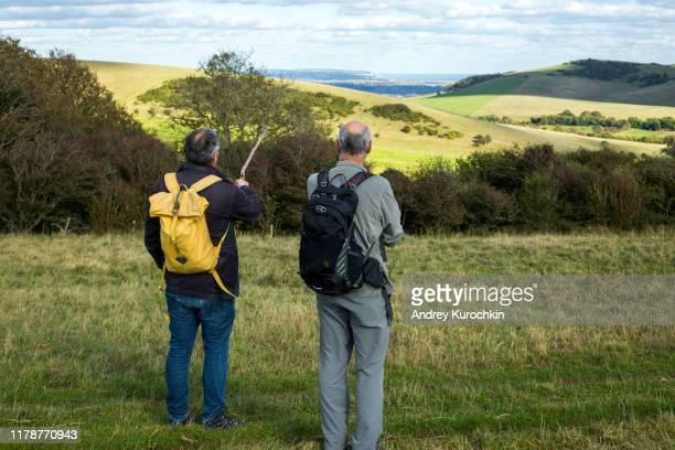 walkers strolling along the south downs way near alfriston, east sussex. - hillsborough sheffield stock pictures, royalty-free photos & images