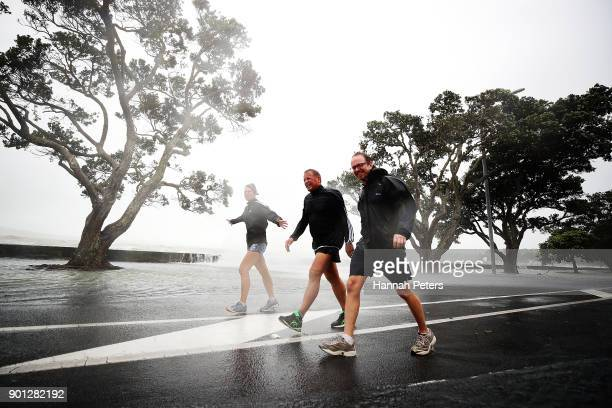 Walkers struggle in the high winds and rain on the waterfront on January 5 2018 in Auckland New Zealand Heavy wind and rain have struck the region...