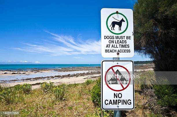 Signs and graphics indicate laws banning camping and dogs on a beach.