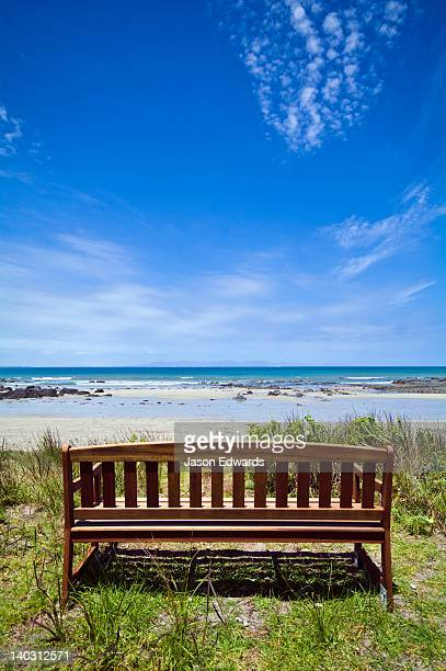 A bench seat on a sand dune overlooks a bright blue ocean in summer.