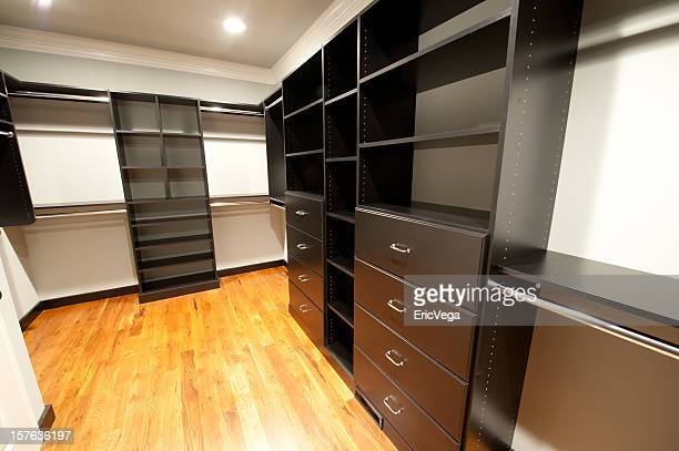 walk-in closet with black wood paneled cabinets - walk in closet stock photos and pictures