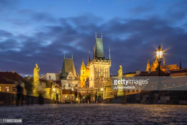 walking across cobbled path of charles bridge at night with historic gatehouse tower - palace stock pictures, royalty-free photos & images