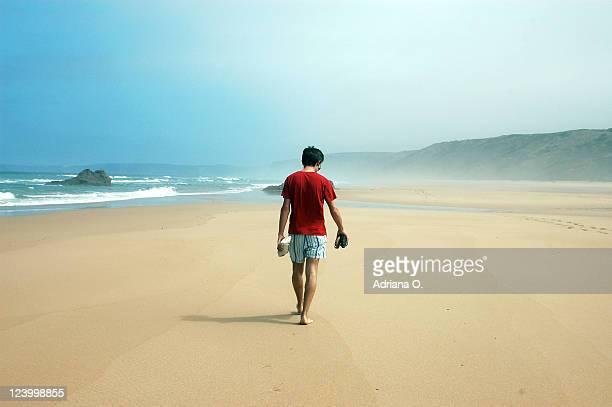 walking alone on bordeira beach - hombre de espaldas playa fotografías e imágenes de stock