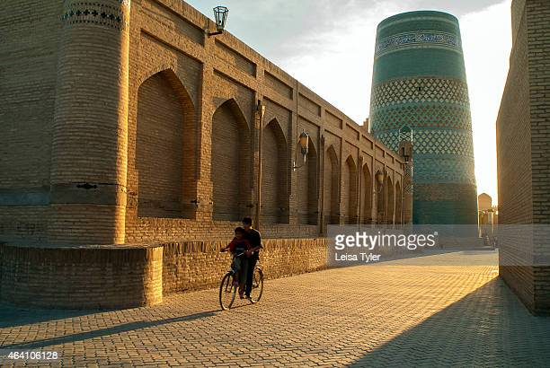 Walking along a deserted street near Kalta Minor Minaret in Khiva at sunset Founded in the 6th century Khiva is a beautiful preserved city in between...
