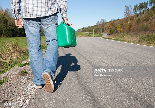Walking along countryside road with petrol can