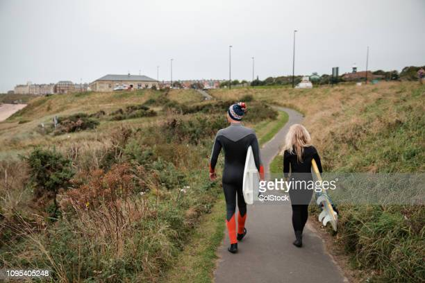 walking along the sea front - surf stock pictures, royalty-free photos & images