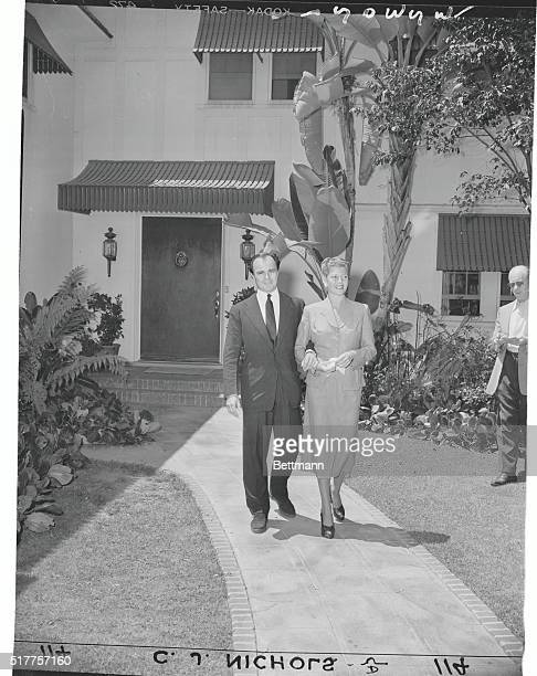 Walking Along Together Hollywood Calif To the tune of popping flashbulbs Rita Hayworth and Aly Khan stroll arm in arm towards waiting newsmen to...