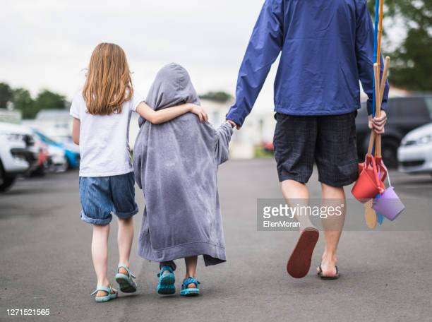 walking back from the beach - rain stock pictures, royalty-free photos & images