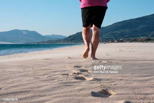 walking bearfoot in the sand at the beach - finn bjurvoll stock pictures, royalty-free photos & images