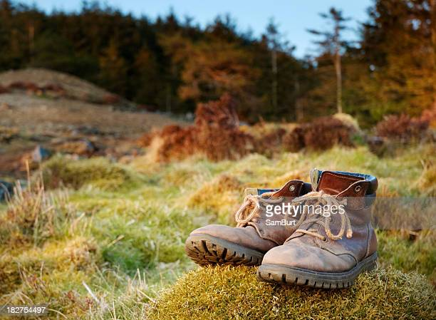 Walking boots left on the grass in the countryside