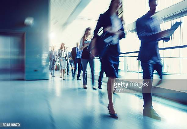 walking business people - motion blur stock photos and pictures