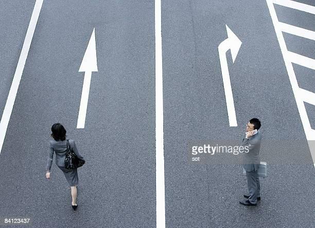 Walking businesswoman and businessman talking mobi