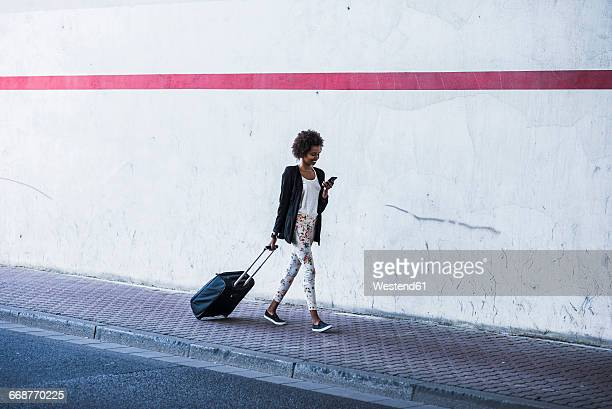 Walking businesswoman with baggage looking at her smartphone