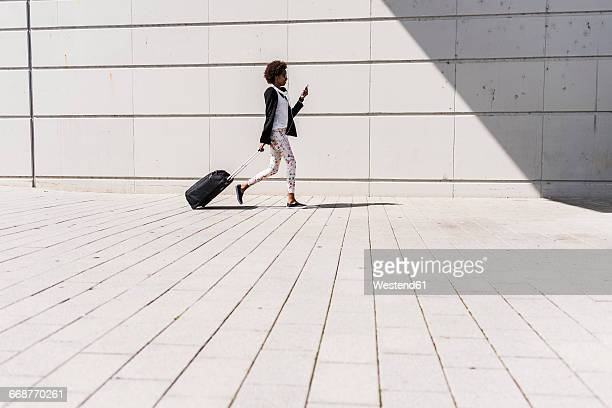 walking businesswoman with trolley bag looking at her smartphone - geschäftsreise stock-fotos und bilder