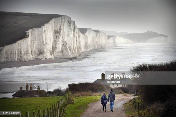 walking couple - seven sisters cliffs stock photos and pictures