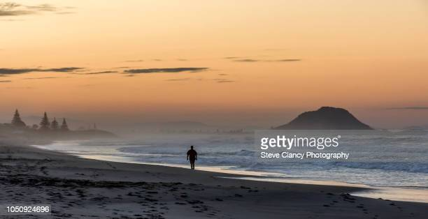 walking down the beach at sunset. - mount maunganui stock pictures, royalty-free photos & images