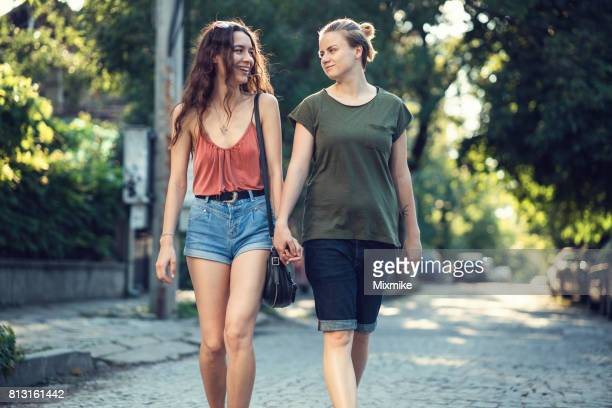 walking hand in hand - women wearing see through clothing stock pictures, royalty-free photos & images