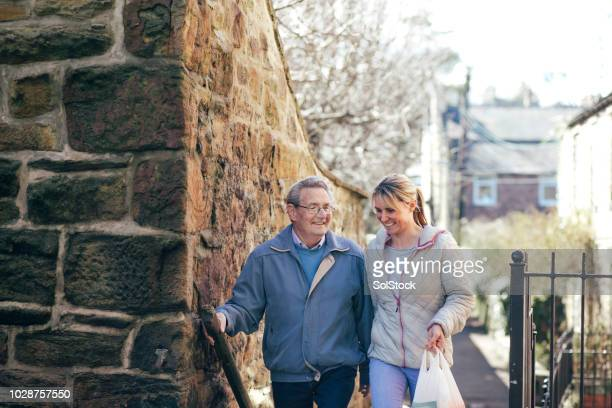 walking home from shopping with his carer - vanguardians stock pictures, royalty-free photos & images