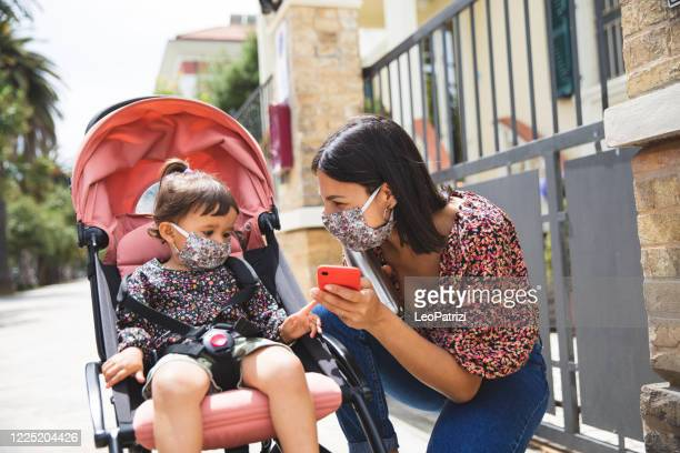 """walking in the city with surgical mask, mother and little daughter in """"new normal"""" life - pushchair stock pictures, royalty-free photos & images"""