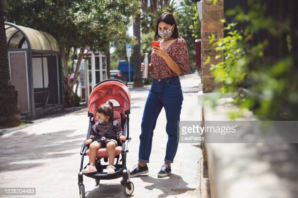 """walking in the city with surgical mask, mother and little daughter in """"new normal"""" life - reusable stock pictures, royalty-free photos & images"""
