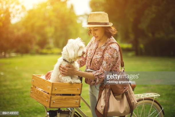 Walking in the park with her Maltese dog