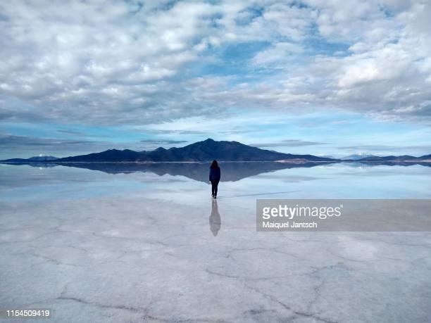 walking in the salar de uyuni with reflection of the sky. - bolivien stock-fotos und bilder