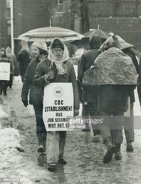 Walking in the slush yesterday outside CBC headquarters on Jarvis St with umbrellas and wearing plastic sheets to shield them from rain and snow CBC...