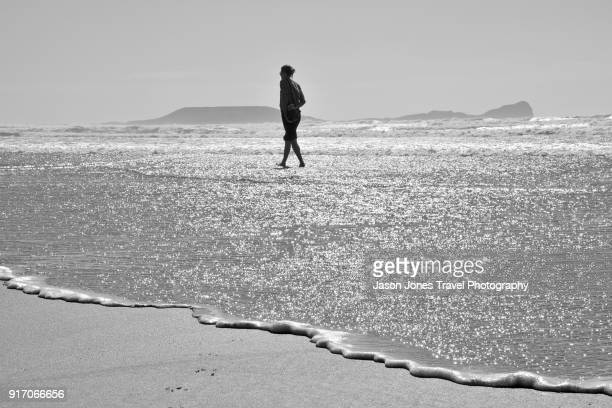 walking in the waves - gower peninsula stock photos and pictures
