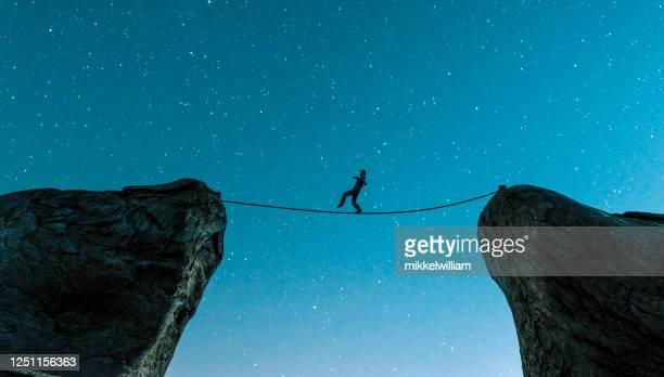 2つの崖の間をロープで歩き、バランスを保つ - 綱渡りのロープ ストックフォトと画像