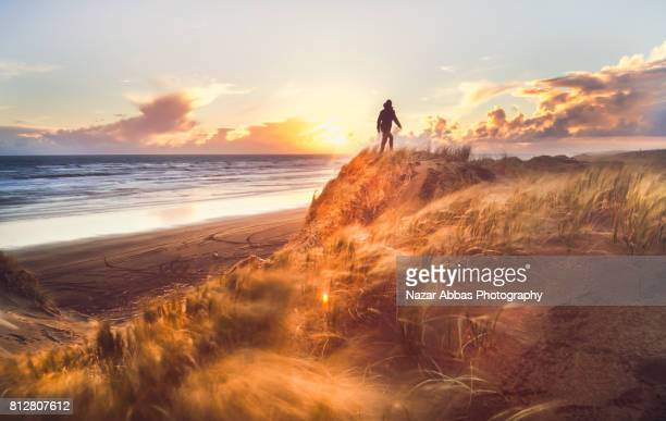 Walking On Sand Dune With Sunset In Background.
