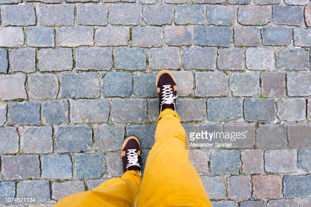 Walking on the cobbled street in sneakers, personal perspective high angle view