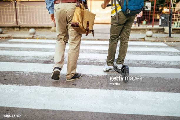 caminando por la cebra cruce en el camino a la escuela - cruzar fotografías e imágenes de stock