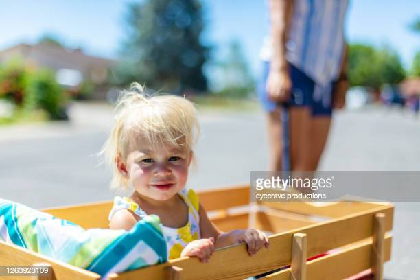 walking outdoors in a western suburban neighborhood a millennial mother and baby boomer grandmother with toddler child in red wagon - eyecrave  stock pictures, royalty-free photos & images