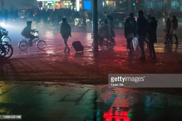 Walking people in the rain at night