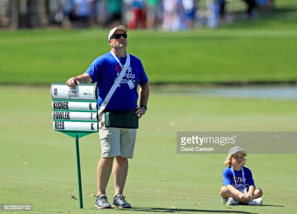 A walking scoreboard bearer with his young helper on the ninth hole during the second round of the 2018 Honda Classic on The Champions Course at PGA...