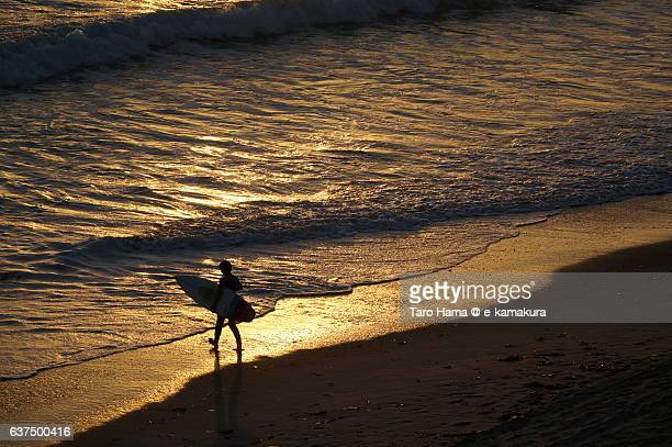 A walking surfer on the sunset beach