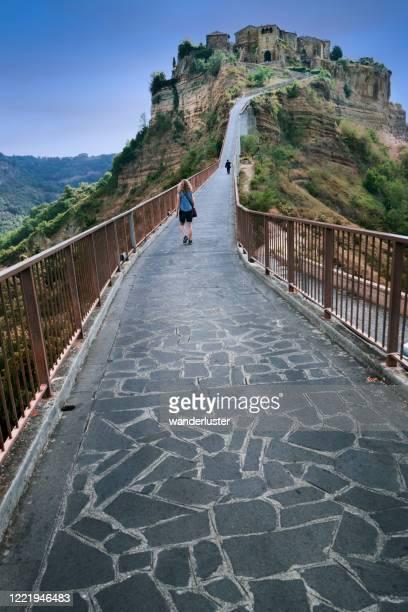 walking the long pedestrian bridge to civita de bagno - civita di bagnoregio foto e immagini stock