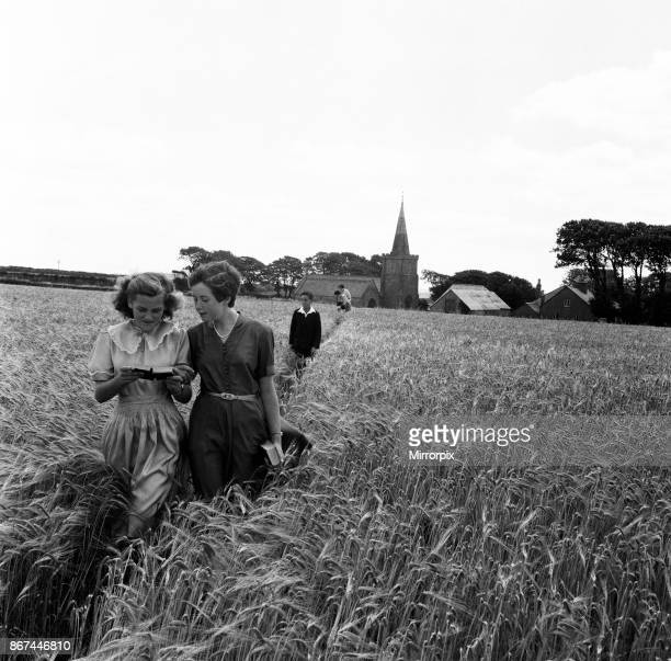 Walking through the barley field at Bigbury South Devon Choirgirls Hannah and Pamela Burgoyne both aged 11 read text of the parson's sermon as they...