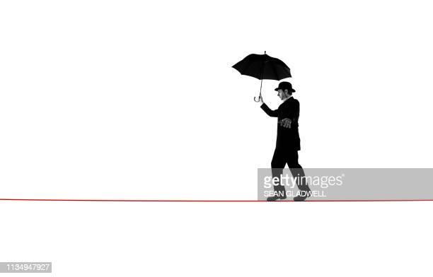 walking tightrope with umbrella - 綱渡りのロープ ストックフォトと画像